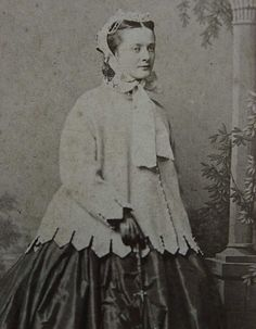 Photo of a blonde-haired woman wearing a Paletot coat over her dress, mid-1800s. The paletot coat was an outdoor garment that fitted the figure.