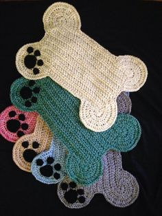 Thick and heavy weight hand crocheted dog bone shaped floor place mat is embellished with black paw print in one corner. Use to place food & water bowls. Other uses include using as a rug cushion in dog crate or great for a floor rug in any room for decor or as a place for your fur baby to