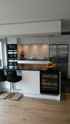 Witte keuken met kookeiland, Amerikaanse koelkast, wijn kast, keukenbar, magnetron / combi stoomoven / heteluchtoven.