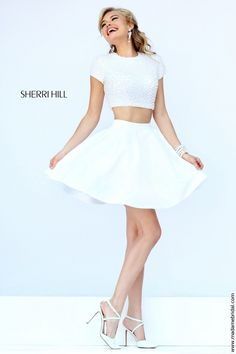 Define your night of fun through the two-piece ensemble comprising the Sherri Hill 32249 short dress. The crop top is richly coated with faux pearls, roaming across the jewel neckline and short sleeves emphasizing the cutout back. Baring the midriff, the fluttering skirt jets off the natural waist then plummets into the cocktail length. Available in Blush and Ivory as shown.