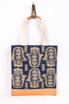"""Every Purchase helps a girl go to school.Half the profits from the purchase of this item funds girls education programs in India. TheHamsa print tote is features a hand-printed original design on cotton canvas / magnetic clasp / zip pocket inside Fully lined inside with waterproof nylon Tan leather bottom, handle trim    Dimensions: 15"""" W / 16"""" H / 9"""" handle drop   Hamsa Canvas Tote by Bloom & Give. Bags - Totes Florida"""