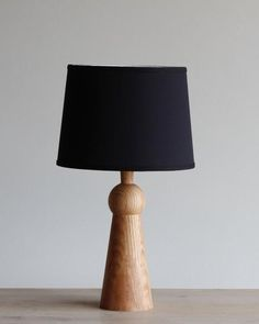 The Bella table lamp has a simple yet elegant design that adds warmth to any bedroom, living room, or office. It is made in Pennsylvania from hand turned oak. Table Lamp Wood, Wooden Lamp, Natural Table Lamps, Lamp Cord, Black Lamps, Wood Lathe, Red Oak, Fabric Shades, Shades Of Black