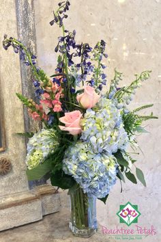 This tall arrangement features lilies, blue hydrangea and delphinium, pink snapdragons and roses, and more. A wonderful housewarming or birthday gift to brighten someone's day.