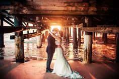 Bride and groom under the boardwalk as the sun sets. // Redondo Beach Historic Library Real Wedding | Zoom Theory Photography