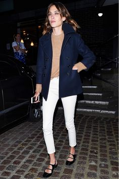 Alexa Chung wears a tan sweater, navy peacoat, white jeans, and black flats