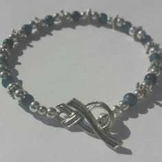 Child Abuse Awareness Bracelet with Ribbon Clasp.  Part of the S & K Awareness Line.  Blue glass beads and silver spacer beads with a silver awareness ribbon toggle clasp.