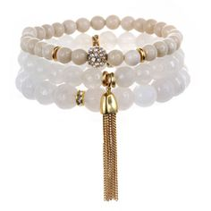 """As seen in O, The Oprah Magazine! Set of 3 semi-precious beaded stretch bracelets with crystal and 22K gold-dipped accents. Available with tassel or gem pendant. White symbolizes protection, offering a sense of peace and calm. It encouragesa tranquil state of mind, full of comfort and hope.  Circumference: 6 1/2"""";bead sizes: 6mm, 8mm, 10mm. Tassel pendant drop: 1 1/2"""";Gem pendant drop: 1/2""""  Materials: Smooth & faceted quartz beads, 22K gold-dipped brass, glass and crystal details."""