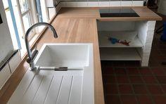 Snedkerlavet køkkenbordplade i egetræ med planlimet vask og integrerede hulkehllister.