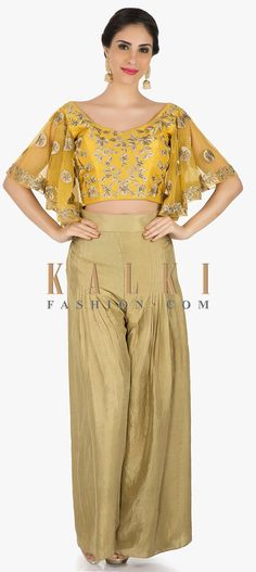 Buy Online from the link below. We ship worldwide (Free Shipping over US$100)  Click Anywhere to Tag Beige Palazzo pants with mustard crop top elevated in resham work only on Kalki This beige palazzo pant with mustard crop top suit is so sangeet ready. The palazzo pants in silk comes in pleated design which brings in a standout style. The mustard crop top is intricately textured using the resham work in floral motifs featuring the much-in-trend bell sleeves.