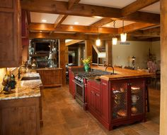 Rustic kitchen made with Knotty Alder wood. Love thus kitchen especially the red center isalnd with the range.