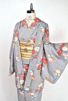 白の糸がネップのように織り込まれたフロスティグレーの地に、椿のような可憐な花枝が織りだされたウールのアンサンブル(着物と羽織のセット)です。
