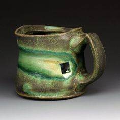 """Stoneware Mug, Green Matte Glaze With Soft Glass And Seashells, Cone 6 Oxidation"", Shadow May Studios on Etsy: ∆ 6 stoneware, electric/oxidation fired, green matte glaze, soft glass applied to the square accent on the mug face, the soft glass forms a large drip and wraps around the surface, sea shell wads are propped under cup to prevent the large drop of soft glass from touching the surface of the kiln shelf, for texture, and for aesthetic effect, $45.00"