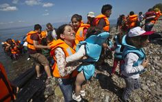 Syrian migrant mother holding her child cheer as they reach the shore of Eftalou beach, 60 kilometers north of the port town of Mytilini after crossing the Aegean from Turkey on the southeastern Greek island of Lesbos, Greece, Sunday, Aug. 23, 2015. Greece this year has been overwhelmed by record numbers of migrants arriving on its eastern Aegean islands, with more than 160,000 landing so far. (AP Photo/Visar Kryeziu)