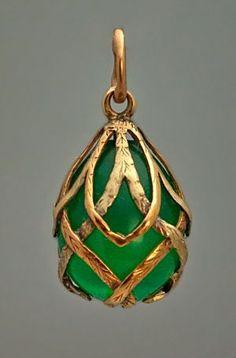 A highly unusual gold and chrysoprase egg pendant. Made in St. Petersburg between 1899 and 1904. An egg-shaped carved chrysoprase (the most valuable variety of chalcedony gemstones) of glowing green color is mounted with two-tone gold interlaced garlands.