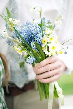 A small posy bouquet of daffodils, snowdrops, and muscari for bridesmaids | Brides.com