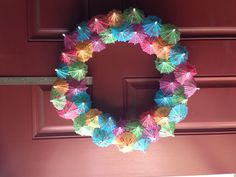 My new spring/summer wreath. Thanks Pinterest! PS: if you have kids older than about 6, they can help unfurl the umbrellas. Mine were leftover from a luau block party, CHEAP at US Toy.