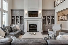 large living room with two story windows  gorgeous grey living room with black fireplace Living Room with Fireplace Design Ideas