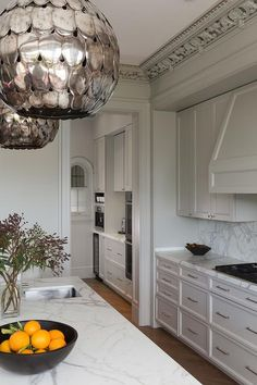 Stunning kitchen features a pair of Soane Owl Lanterns illuminating a white marble top island fitted with a stainless steel prep sink.