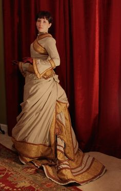 Draped and patterned based on a fashion print from the 1870s, this bustle gown is covered in trimming.