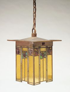 """GUSTAV STICKLEY: Rare and exceptional four-sided lantern with an overhanging hammered copper top on panels of hammered amber leaded glass, depicting stylized flowers in reds and greens. Original patina, some looseness to corners. Complete with original chain and square ceiling cap. Circular Craftsman stamp. Lantern: 13"""" x 10 1/4"""" x 10 1/4"""", with chain: 37 1/2"""" ht."""