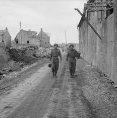 Cine cameramen Sgt Ernest Walter and Sgt A C Gross, of No 5 Army Film and Photographic Unit, walk though through the ruined village of Lebisey with their cameras during the assault on Caen, France.