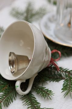 DIY Tea cup bell. Drill a hole in a tea cup and hang a bell on a piece of ribbon. Top with a bow. From Sjarmerende jul.