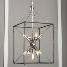 """Starburst Light Ray Hanging Lantern Light radiates from a starburst cluster of 9 mini tubular bulbs (included) inside a black iron cage. Polished Nickel or Aged Brass """"Sputnik"""" cluster adds a midcentury modern touch"""