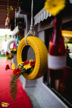 Painted tyre with florals as décor | WedMeGood| #wedmegood #indianweddings #decor #florals #mehendi #unique #bright #colourful #tyre #flowers #hangingdecor