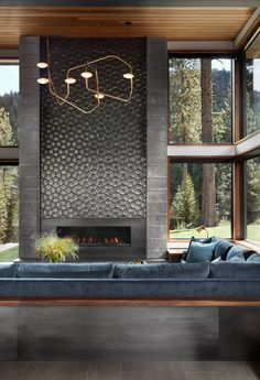 Fabulous prefabricated mountain modern home on Lake Tahoe A floor-to-ceiling fireplace, which doubles as an art piece, features dimensional tile by Daniel Ogassian. The tile is banded on either side by board-formed concrete. Home Fireplace, Living Room With Fireplace, Fireplace Surrounds, Grey Fireplace, Fireplace Ideas, Fireplace Feature Wall, Sunken Living Room, Fireplace Outdoor, Concrete Fireplace