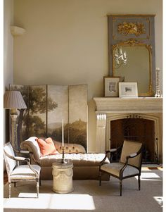 A hand-painted screen frames a small sitting area in the living room and acts as a backdrop to the Edward Ferrell Chiswick chaise. The pair of chairs can move easily from one sitting area to another. Stone Cypress side table from Dennis & Leen.