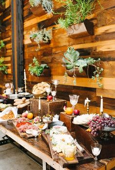 An eclectic cheese and prosciutto station with assorted fruit displayed against a wall of wild succulents.