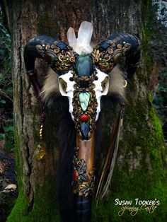 The SACRED RAM Staff features a genuine ram skull which has been crowned with a Frosted Quartz Crystal cluster. Two flashing Labradorites occupy the front of the skull, as well as a polished Black Tourmaline and a Carnelian cabochon. Two fossil Ammonites serve as the eyes. Embedded in the ornamentation on the horns are two Black Tourmalines and two Agate cabochons. The horns have also been wrapped with leather and ornamentation. Four dangles hang from the horns that include River Am...
