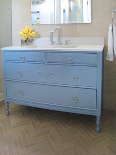 The key to upcycling is being able to see the beauty in an old, damaged piece of furniture. Erinn Valencich found an old cabinet at a flea market and repurposed it as an antique bathroom vanity, bringing a charming look to this bathroom.
