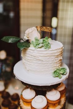 cake topping a cupcake tower, photo by With Love & Embers http://ruffledblog.com/ostertag-vistas-wedding #weddingcake #desserts