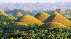 Chocolate Hills, Ile de Bohol, Philippines. Cette formation est composée de 1 268 collines en forme de cône de tailles similaires (qui a dû en comporter plus de 1 700 par le passé). Ces collines sont réparties sur plus de 50 kilomètres carrés. Elles doivent leur nom à leur forme et à la végétation qui devient brune vers la fin de la saison sèche.