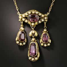 Arts and Crafts? Victorian? A mix of both? Whatever the era, this is one eye-catching necklace. Vibrant, gleaming purple-hued garnets and pearls are used to create a striking and uncommon design. The centerpiece features a horizontally set cushion-cut garnet in a frame of seed pearls, with three pear-shaped garnets accented with pearls swinging freely below. The 18 1/2-inch chain is also dotted with seed pearls.