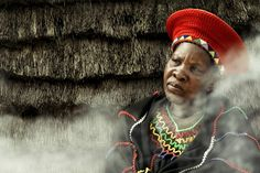 Africa | Zulu woman pondering in front of the fire.  KwaZulu Natal, South Africa |  ©Dion Bekkers