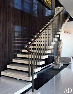 Travertine stairs appear to float next to an ebony-paneled wall in the gallery of a Manhattan duplex designed by architect Carlos Aparicio. A Roman togatus statue and 1924 gold-leafed murals by José María Sert offset the modernity of the staircase. (April 2011)