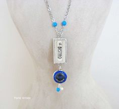 A fun and unique necklace with a framed image of a vintage sign with the text LE BISTRO on one side, and an the text RIVE GAUCHE on on the reverse side. Below hangs a blue de Venoge Champagne cap on one side, and a silver colored Champagne cap on the reverse side.
