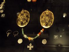 Woman's dress accessories found in a grave from the second half of the 10th century, in Kiev, Ukraine. Next to her typically Scandinavian brooches, the woman wore rings of eastern origin with her headscarf, a row of glass, amber, carnelian and rock-crystal beads, and two Byzantine coins. The cross indicates she was a Christian. Photo from the Viking exhibition in the National museum of Copenhagen.