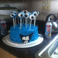 Monster Cake (home-made / non professional) eyeballs are donut holes on lollipop sticks that we frosted. Cute addition: monster has same teeth as the bday boy (1yo).