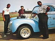 "Doug Cook, center, with Mr. Tim Woods and Mr. Fred Stone, owners of the Stone, Woods and Cook gasser. Mr. Stone and Mr. Woods did not get the publicity they so richly deserved. S-W-C is one of the most famous cars in all of drag racing, and very few ever knew that Stone and Woods were African American. Doug ""Cookie"" Cook was a very talented driver and mechanic for the team."