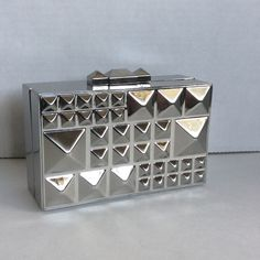 """BCBGMaxAzria Dee Pyramid Clutch Prove your fashion mettle by keeping this pyramid-studded wonder close at hand.  Rectangular clutch. Metal exterior with pyramid studs throughout. Top clasp closure. Material: Iron alloy. Approximate dimensions:  4"""" W. 6"""" H. 2.75"""" D. BCBGMaxAzria Bags Clutches & Wristlets"""