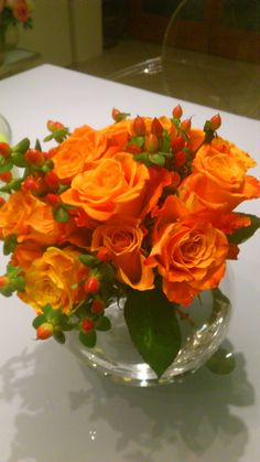 rustic bridal bouquet with orange roses and red hipericum berries