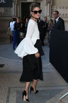 Olivia tucked a flowing peplum L'Academie top into black culottes for a dramatic effect while out at Paris Fashion Week.
