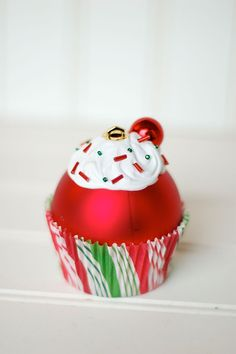 "diy cupcake ornament: red ball ornament glued to a cupcake liner, then apply caulk ""frosting"", bead sprinkles and tiny cherry ball on top!"