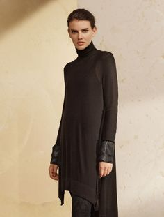 - Description - Details - Customer Care This luxurious sweater starts as a turtleneck but flows down into a tunic with side slits and a flattering high-low hemline. Pair it with our Suede Skinny Pants