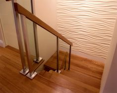Stair with textured wall and glass hand rail by Faulding Architecture