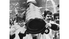 Canadian hockey players Bobby Clarke (left) and Bernie Parent of the Philadelphia Flyers carry the Stanley Cup as they celebrate their series-winning victory over the Boston Bruins, Philadelphia, Pennsylvania, May 19, 1974. (Photo by Bruce Bennett Studios/Getty Images)