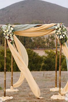 Layers of olive green and cream fabric are accented with two floral arrangements to create a natural feeling arbor. Altar, Wedding Decorations